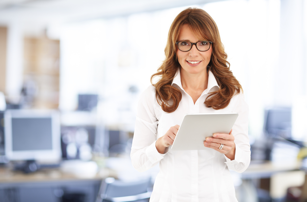 Portrait of middle age businesswoman holding digital tablet and standing at office.