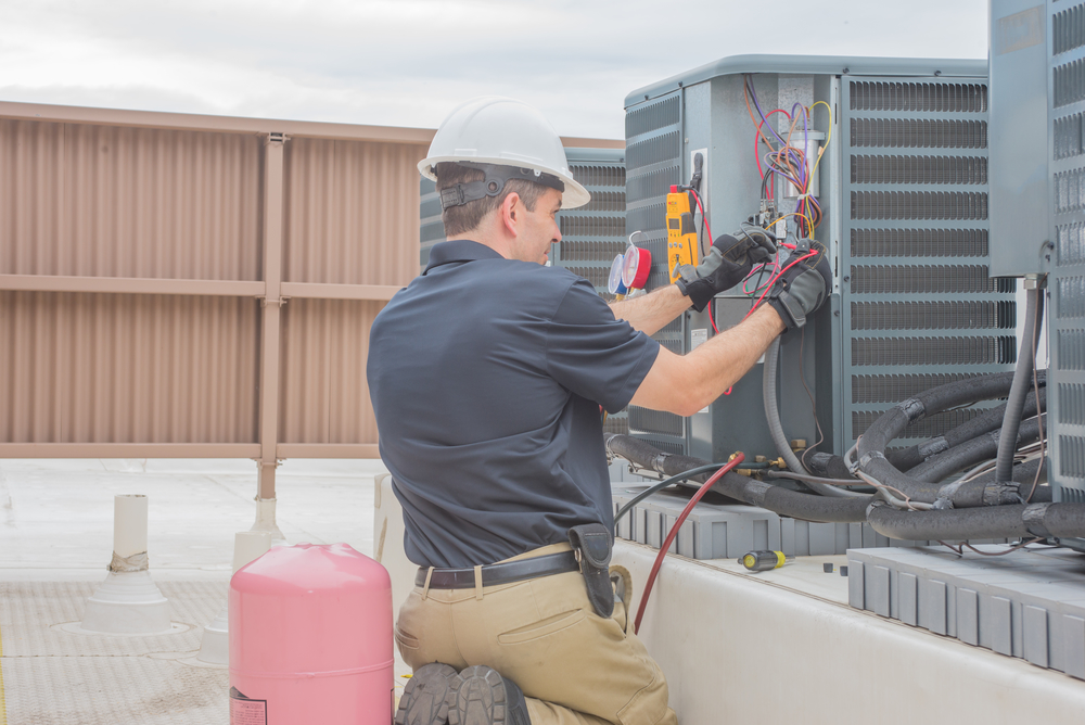 HVAC Technician checking for power on a rooftop condensing unit.