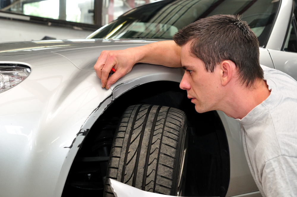 Car insurance agent assessing car damages