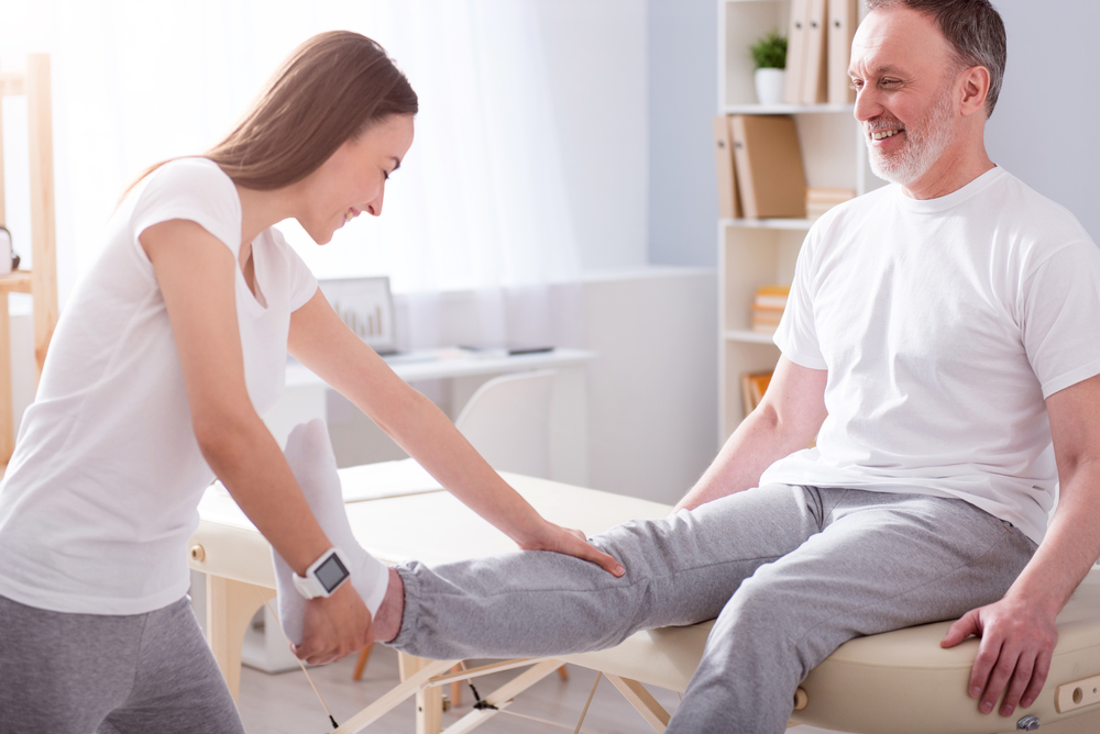 Occupational Therapy Assistant helping a patient with streched leg