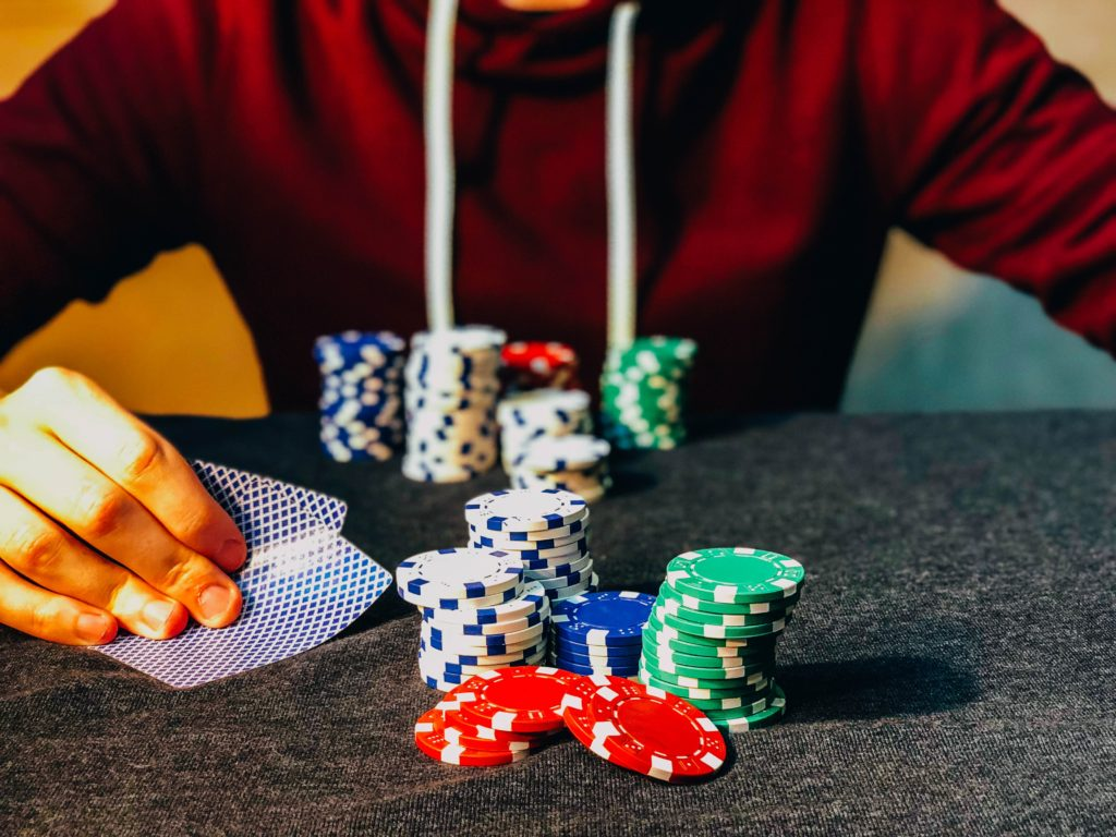 Young male hand visible playing poker with some stacks