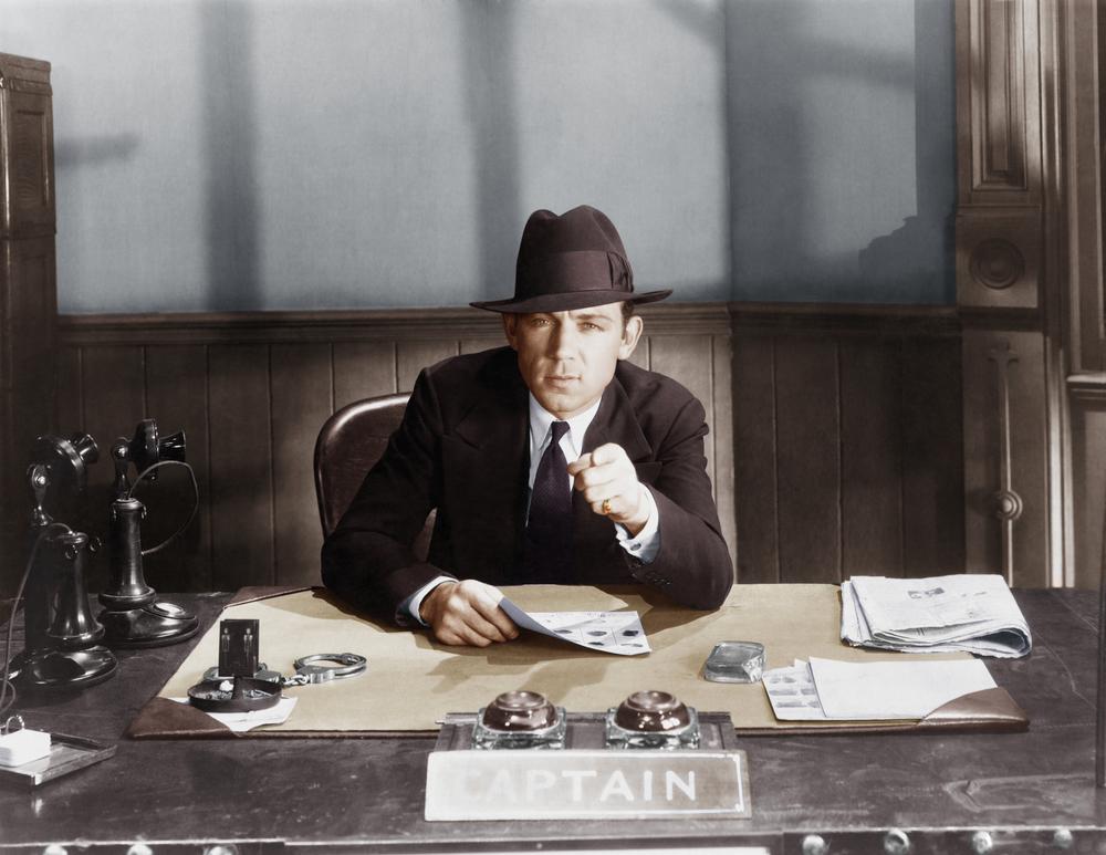 oldskool detective behind a desk