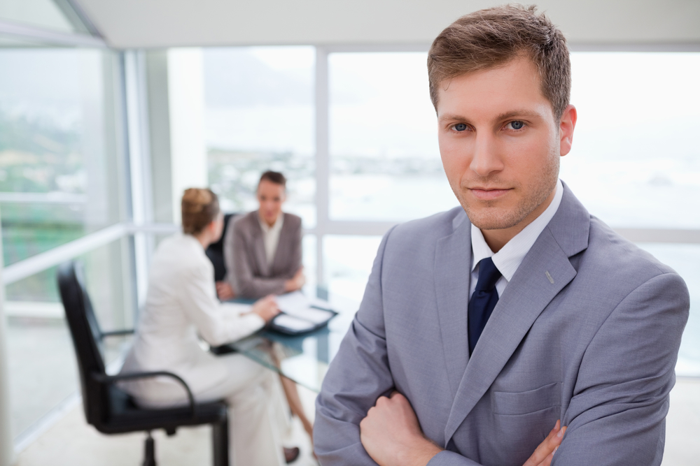 Young sales manager standing with his team sitting behind him