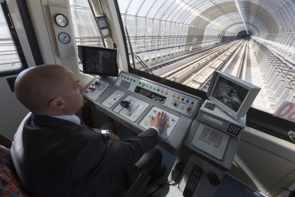 Subway train operator visible from behind driving underground in a new tunnel