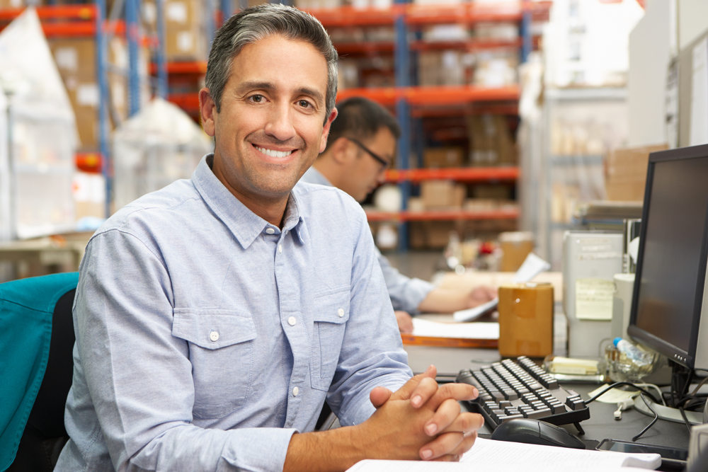 Supervisor or manager in a warehouse smiling at the camera