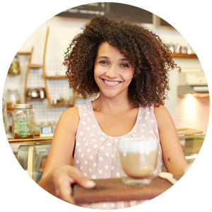 Barista lady smiling to the camera and holding coffee